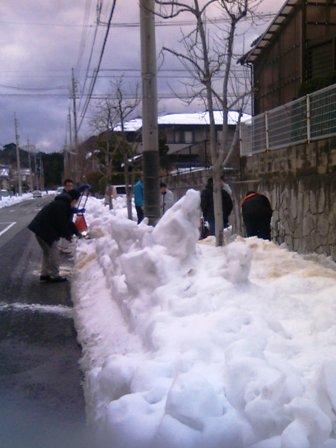 歩道の除雪をするオトナたち