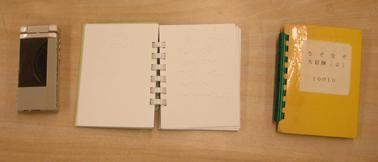 写真:点字なぞなぞの本。携帯電話と大きさくらべてみました。